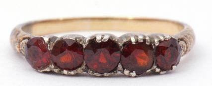 Antique garnet ring, featuring five round faceted garnets raised between carved scroll shoulders