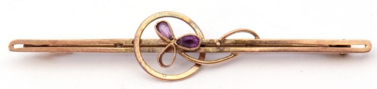 9ct stamped amethyst brooch of open work design, centring an amethyst set flower (one stone missing)