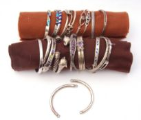 Twenty one various white metal hinge and torque style bracelets and some bangles with inlaid and