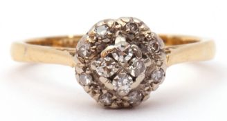 Diamond cluster ring featuring 4 small circular diamonds, raised above a small diamond surround,