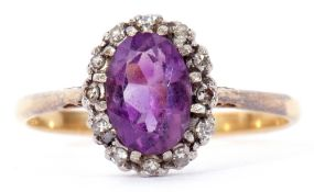 Antique amethyst and diamond cluster ring, the oval faceted amethyst within a surround of 12 small