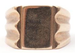 Large 9ct gold gent's signet ring, the plain polished rectangular panel raised between carved and