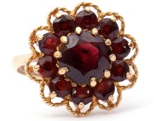 9ct gold garnet cluster ring, the central faceted round garnet within a small garnet surround,