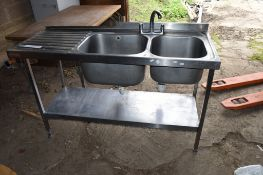 Large stainless steel double Sink, on stand with single drainer to left.
