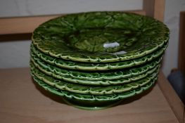 GROUP OF GREEN POTTERY PLATES MODELLED IN RELIEF WITH LEAVES