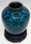 Large Persian pottery globular vase with metal rim, the vase decorated with a fish design on green