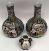 Two Japanese porcelain baluster vases, decorated with panels of Japanese figures, the green ground