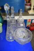 CUT GLASS WARES INCLUDING FOUR DECANTERS AND STOPPERS, AND FRUIT BOWLS