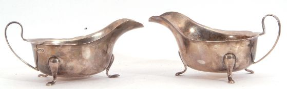 Pair of George VI silver sauce boats each with card cut rims and scroll handles standing on three