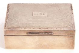 Silver cigarette box, the engine turned hinged lid with central initialled and engraved cartouche,