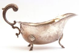 George V silver sauce boat with shaped card cut rim, flying leaf capped scroll handle, standing on