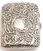 Victorian silver repousse cigarette case of rectangular form decorated both sides with scrolls,