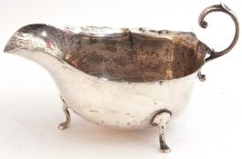 George VI silver sauce boat with shaped rim and capped flying scroll handle, on three cast hoof