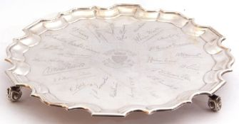 George V presentation silver salver, a round body with a Chippendale style border, standing on three