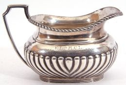 Edward VII silver cream jug of oval form, half fluted piped body and gadrooned lip with angular