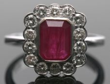 18ct white gold, ruby and diamond cluster ring, the rectangular cushion cut ruby bezel set and
