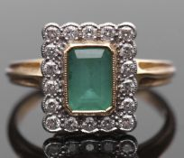 Emerald and diamond cluster ring, the rectangular step cut emerald bezel set and millegrained edged,