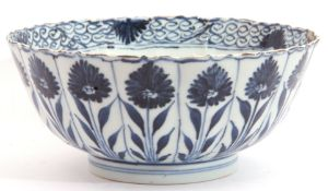A Chinese porcelain bowl, Kangxi, the fluted body decorated with alternating flowerheads in Ming