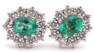 Pair of emerald and diamond cluster earrings featuring an oval emerald, 1.15ct total, each within