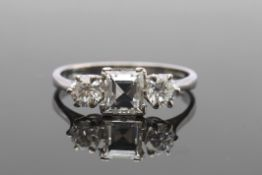 Diamond three-stone ring featuring a square step cut diamond, 1ct approx, flanked by two round