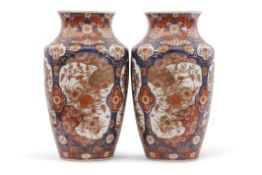 Pair of Japanese porcelain vases with Imari type design in panels with flowers on a blue ground,
