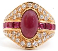 18ct gold ruby and diamond cluster ring, the oval shaped panel centring a cabochon ruby, flanked