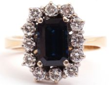 Precious metal sapphire and diamond cluster ring, the rectangular cut sapphire set within a border