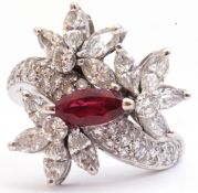 Precious metal, ruby and diamond cluster cocktail ring, centring a marquis shaped ruby raised