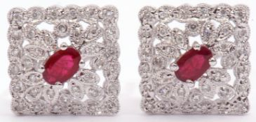 Pair of diamond and ruby cluster earrings, an off-square design centring an oval faceted ruby within