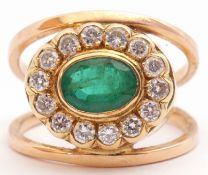 Emerald and diamond cluster ring, a stylised design, the centre with an oval faceted emerald, 8mm