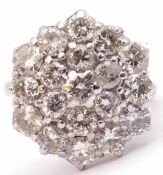 Diamond cluster ring, the circular panel set with three tiers of round brilliant cut diamonds,