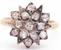 Antique diamond star cluster ring featuring 13 old mine cut diamonds in claw and grain settings,