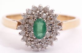 18ct gold emerald and diamond cluster ring, centring an oval faceted cut emerald raised above two