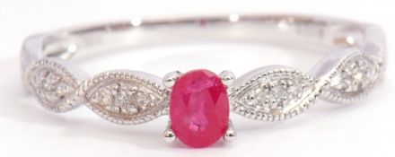 Modern ruby and diamond set ring centring an oval faceted ruby, raised between small diamond set