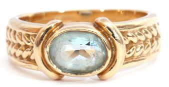 9ct gold and blue stone ring, the oval faceted stone bezel set and raised between rope twist