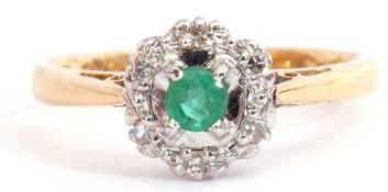 Modern 18ct gold emerald and diamond cluster ring, the round cut emerald four claw set and raised