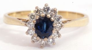18ct gold sapphire and diamond cluster ring, the oval faceted sapphire multi-claw set above a