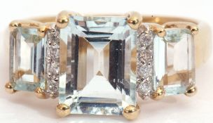 9ct gold pale blue stone and diamond ring, a design with three graduated emerald cut pale blue