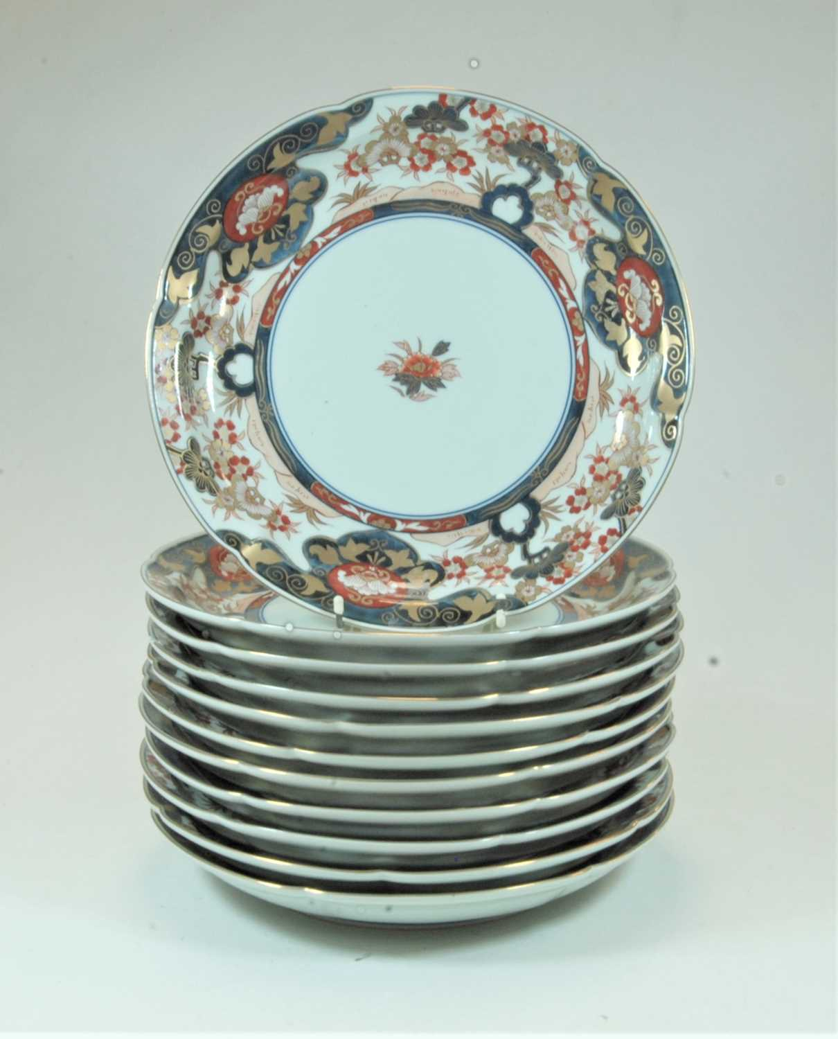 Lot 33 - A set of 12 Japanese plates of shaped circular form decorated in the Imari palette in shades of iron