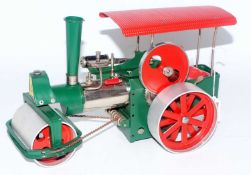 A Wilesco Old Smoky steam roller traction engine comprising of cream chrome and red body complete