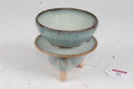 A Chinese stoneware flambe style stem cup of circular form mounted on similarly glazed tripod