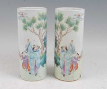 A pair of Chinese vases each of cylindrical form, enamel decorated with two figures beneath a