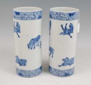 A pair of Chinese blue & white vases each of cylindrical form decorated with various horses within