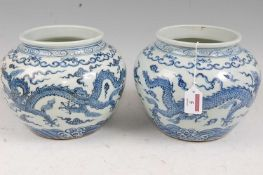 A pair of Chinese export blue & white jardinières, each of squat circular form, decorated with
