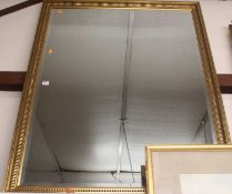 A gilt framed and bevelled rectangular wall mirror, 126 x 100cm