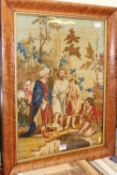 A 19th century woolwork panel, depicting a figure landscape scene, housed in a birdseye maple glazed