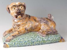 A French faience model of a recumbent pug dog upon a cushion, having all-over sponged decoration (