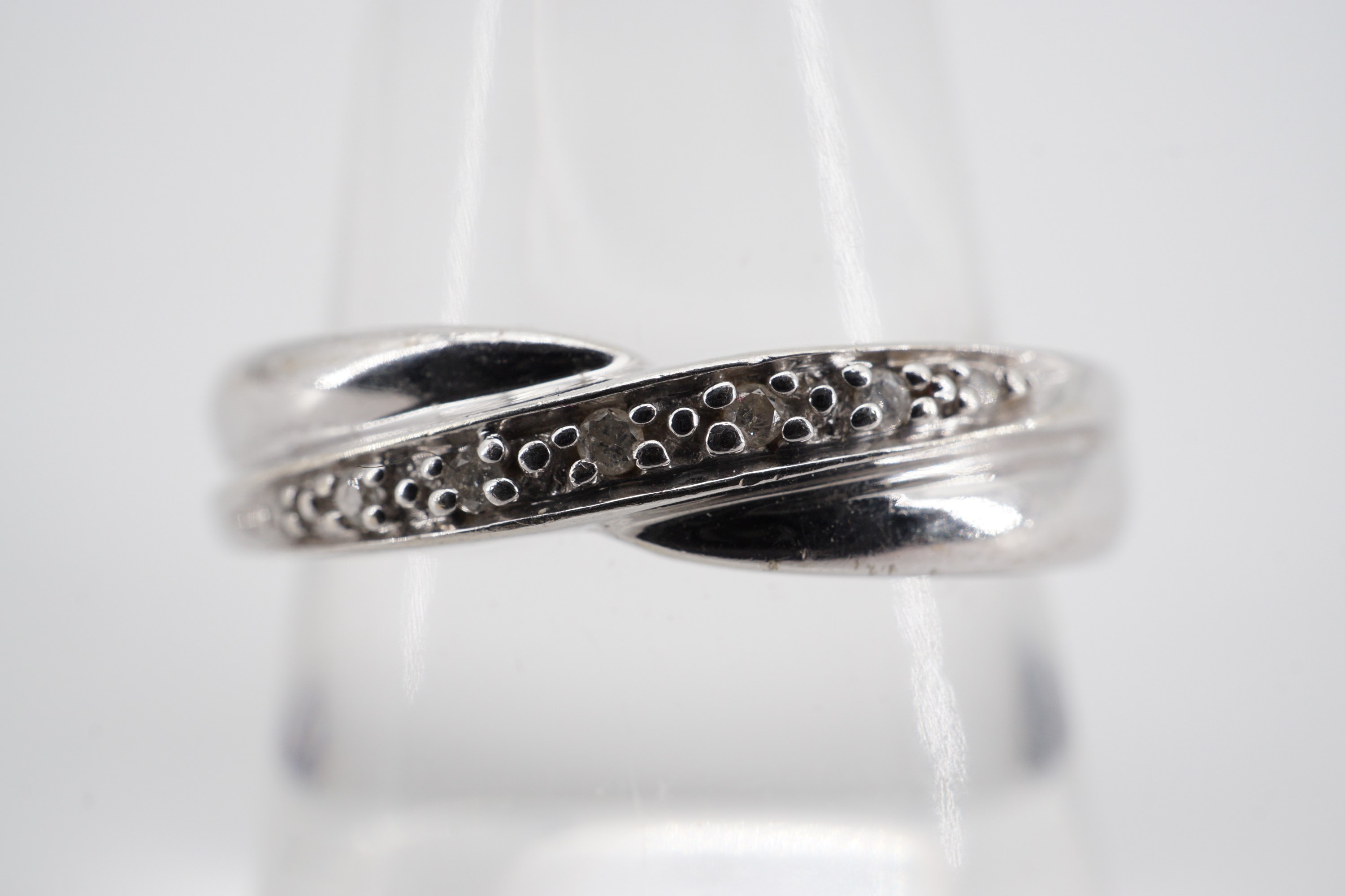 Lot 733 - A contemporary 9ct white gold and diamond eternity ring, the face being twist-set in a saltire