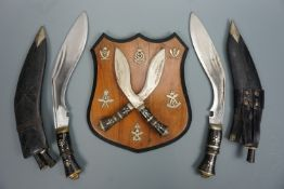 A plaque mounted with crossed kukris and Gurkha cap badges together with two further kukris