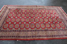 Pakistan Bokhara design carpet having four rows of twelve gols with multiple borders on a wine